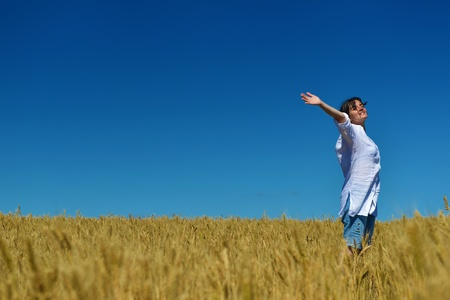 Young woman standing jumping and running  on a wheat field with blue sky in  background at summer day representing healthy life and agriculture concept Stock Photo - 15558242