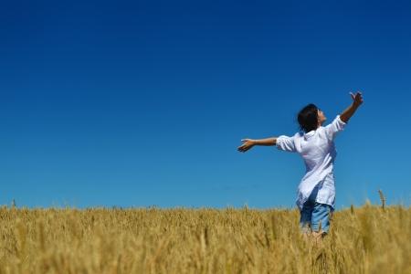 wheat harvest: Giovane donna in piedi saltando e in esecuzione su un campo di grano con cielo blu sullo sfondo al giorno d'estate rappresentare concetto di vita sana e agricoltura