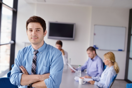 Portrait of a handsome young  business man  on a meeting in offce with colleagues in background Stock Photo - 15301075