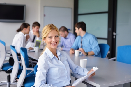 team working together: business woman  with her staff,  people group in background at modern bright office indoors Stock Photo