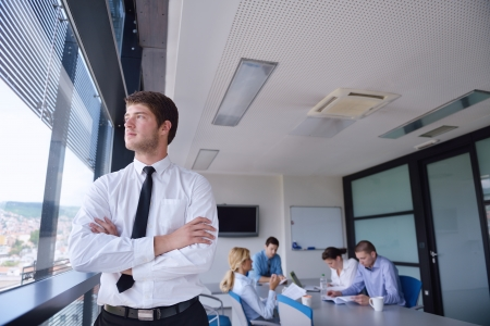 Portrait of a handsome young  business man  on a meeting in offce with colleagues in background Stock Photo - 15301097