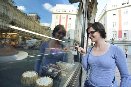 bakery shop: urban scene of young woman in front of sweet candy food store window