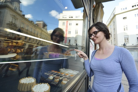 bakery store: urban scene of young woman in front of sweet candy food store window