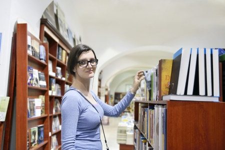 Pretty female student standing at bookshelf in university library store shop  searching for a book Stock Photo - 15587617