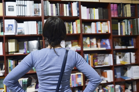 book shop: Pretty female student standing at bookshelf in university library store shop  searching for a book Stock Photo
