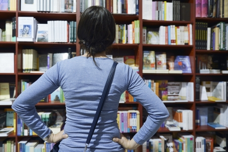 Pretty female student standing at bookshelf in university library store shop  searching for a book Stock Photo - 15587619