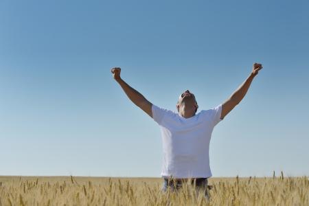 persona alegre: hombre joven en campo de trigo que representa la agricultura éxito y el concepto libertad