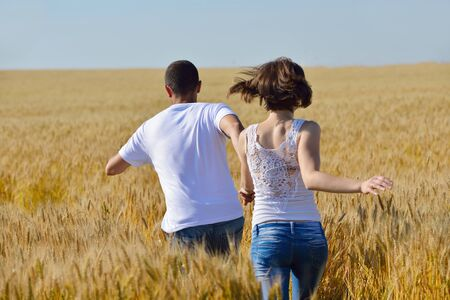 happy young couple in love have romance and fun at wheat field in summer photo