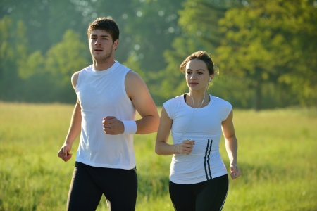 Young couple jogging in park at morning. Health and fitness concept photo