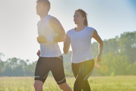 personas trotando: Joven pareja trotar en el parque en la ma�ana. Salud y concepto de fitness Foto de archivo