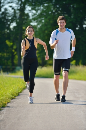 healthy life: Young couple jogging in park at morning. Health and fitness concept
