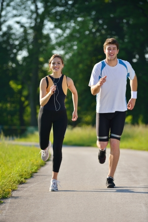 training shoes: Young couple jogging in park at morning. Health and fitness concept