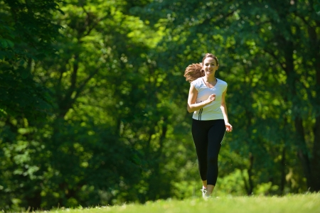 Young beautiful  woman jogging on morning at  park. Woman in sport outdoors health concept photo