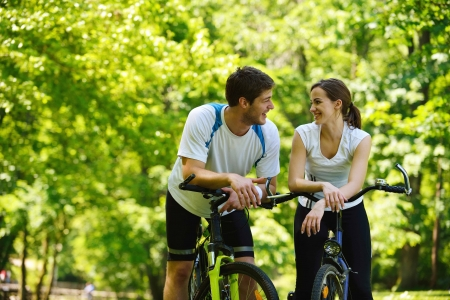active girl: Happy couple ride bicycle outdoors, health lifestyle fun love romance concept
