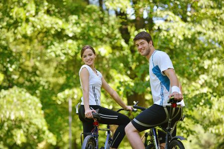 Happy couple ride bicycle outdoors, health lifestyle fun love romance concept photo