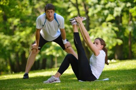estiramientos: pareja joven haciendo salud ejercicios de estiramiento y relajaci�n calentarse despu�s de trotar y correr en el parque Foto de archivo
