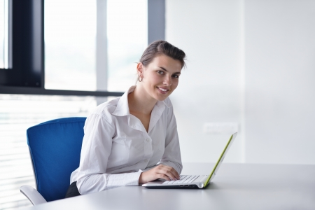 Young pretty business woman with notebook in the bright modern office indoors photo