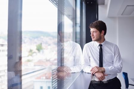 entreprise: heureux de travail jeune homme d'affaires dans le bureau moderne sur l'ordinateur