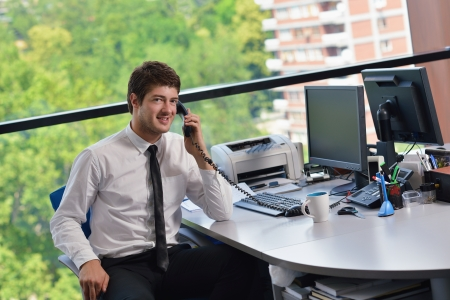 office phone: happy young business  man work in modern office on computer Stock Photo