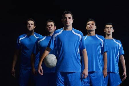 joueurs de foot: groupe de joueurs de l'�quipe de football isol� sur fond noir Banque d'images