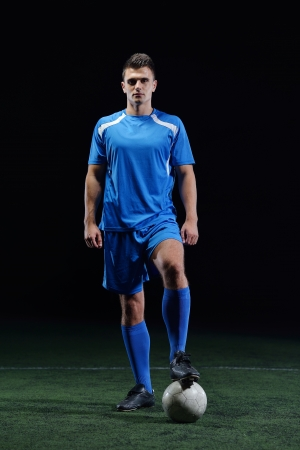 soccer kick: soccer player doing kick with ball on football stadium  field  isolated on black background