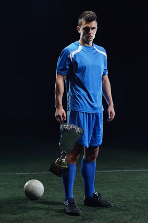 soccer player doing kick with ball on football stadium  field  isolated on black background Stock Photo - 17394551