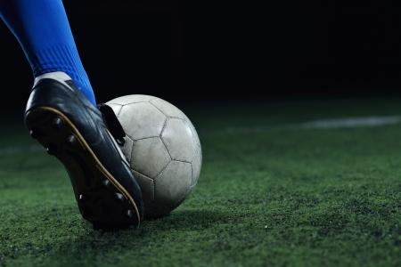 balon soccer: jugador de fútbol haciendo patada con balón en campo de fútbol del estadio aisladas sobre fondo negro