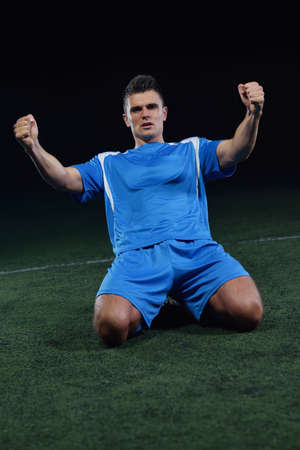 soccer player doing kick with ball on football stadium  field  isolated on black background Stock Photo - 23224766