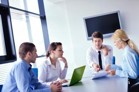 conferencia de negocios: Grupo de felices j?venes empresarios en una reuni?n en la oficina