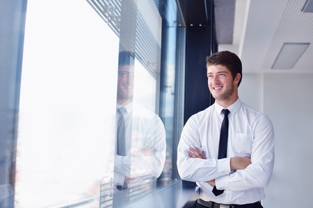 office window view: happy young business  man work in modern office on computer Stock Photo