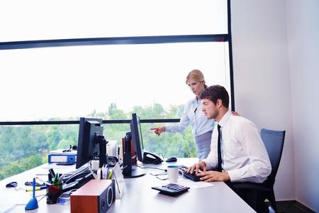 business man laptop: Grupo de felices j?venes empresarios en una reuni?n en la oficina