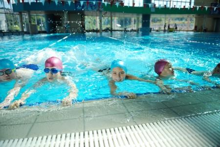 meisje zwemmen: gelukkige kinderen groep bij zwembad klasse leren zwemmen Stockfoto