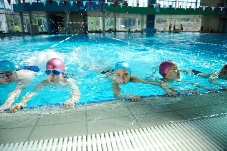 to swim: happy childrens group  at swimming pool class  learning to swim