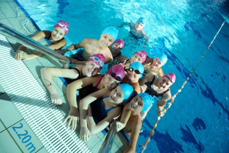 Fat kid: happy childrens group  at swimming pool class  learning to swim