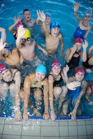 niños nadando: grupo de niños felices en clase de natación de la piscina para aprender a nadar