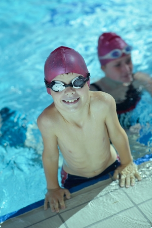 ni�os nadando: chid feliz se divierten en piscina Foto de archivo