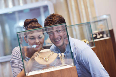 happy young romantic couple in love buy jewelry ring in luxury store photo