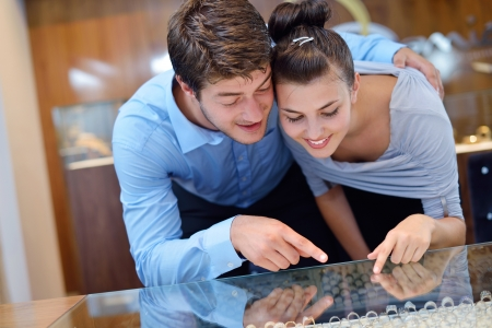 store display: happy young romantic couple in love buy jewelry ring in luxury store