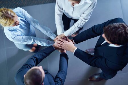 business people group joining hands and representing concept of friendship and teamwork,  low angle view Stock Photo - 16522875