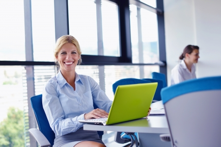computer training: business woman  with her staff,  people group in background at modern bright office indoors Stock Photo