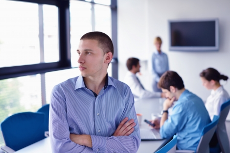 Portrait of a handsome young  business man  on a meeting in offce with colleagues in background Stock Photo - 16522891