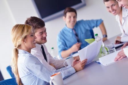 reunion de trabajo: Grupo de felices j?venes empresarios en una reuni?n en la oficina