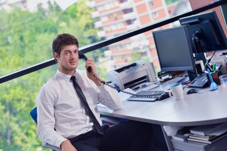 man with phone: happy young business  man work in modern office on computer Stock Photo
