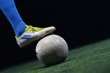 patada: jugador de f�tbol haciendo patada con bal�n en campo de f�tbol del estadio aisladas sobre fondo negro