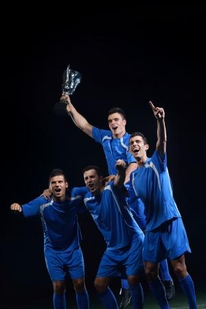 groupe de joueurs de l'équipe de football célébrant la victoire et de devenir champion du jeu tout en tenant coup gagnant