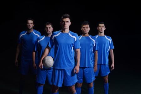soccer: fútbol grupo los jugadores del equipo aislado sobre fondo negro Foto de archivo