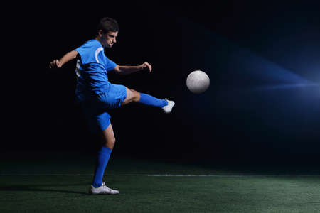 soccer player doing kick with ball on football stadium  field  isolated on black background Stock Photo - 17368392