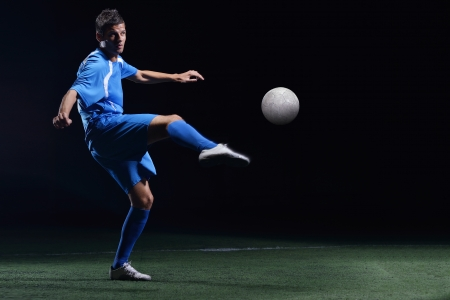 team winner: soccer player doing kick with ball on football stadium  field  isolated on black background