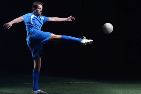 soccer player doing kick with ball on football stadium  field  isolated on black background Stock Photo - 16715140