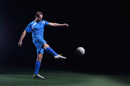 sports wear: soccer player doing kick with ball on football stadium  field  isolated on black background